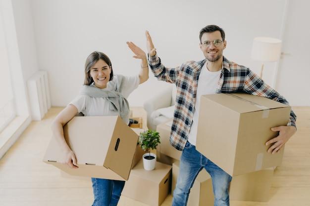 Vrolijke jonge vrouw en man geven high five, glimlachen aangenaam naar de camera, gekleed in vrijetijdskleding, beginnen een nieuw leven