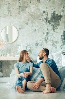 Vrolijke jonge vrouw en man zitten op blote voeten bij het bed en ontspannen tijdens het praten