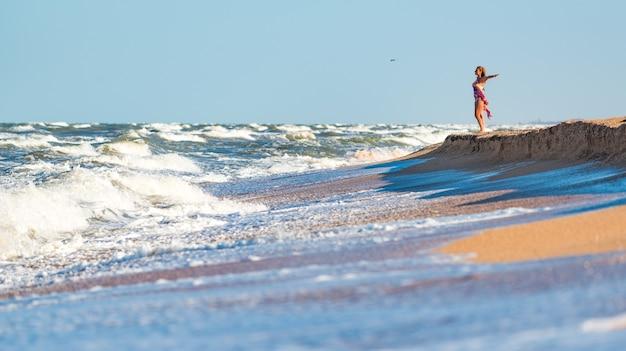 Vrolijke jonge vrouw geniet van de stormachtige golven van de zee die op een zonnige zomerdag ver achter de horizon kijken terwijl ze ontspant op de zee. concept van vakantie en privacy. copyspace