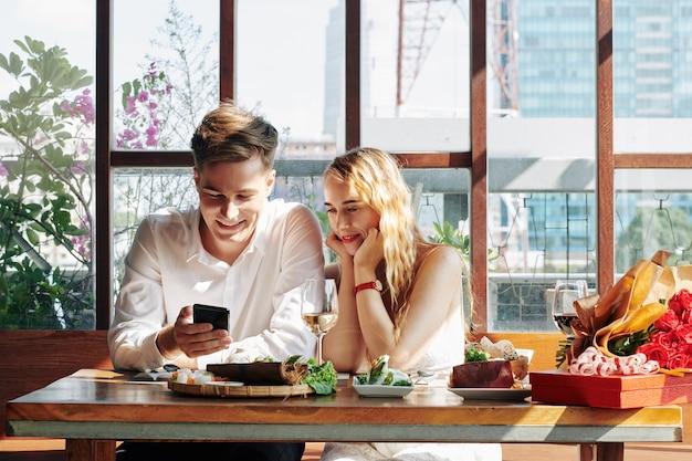Vrolijke jonge vrouw genieten van diner in café en kijken naar grappige video's op smartphone