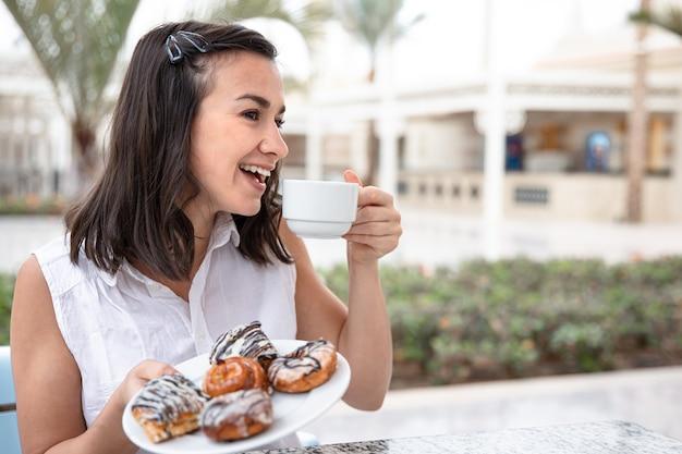 Vrolijke jonge vrouw genieten van koffie in de ochtend met donuts op het terras.