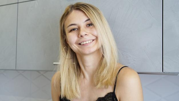 Vrolijke jonge vrouw glimlachend en kijken naar camera in gezellig ingerichte keuken