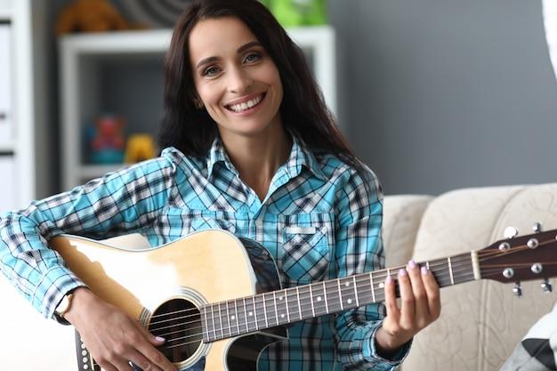Vrolijke jonge vrouw het spelen gitaar thuis