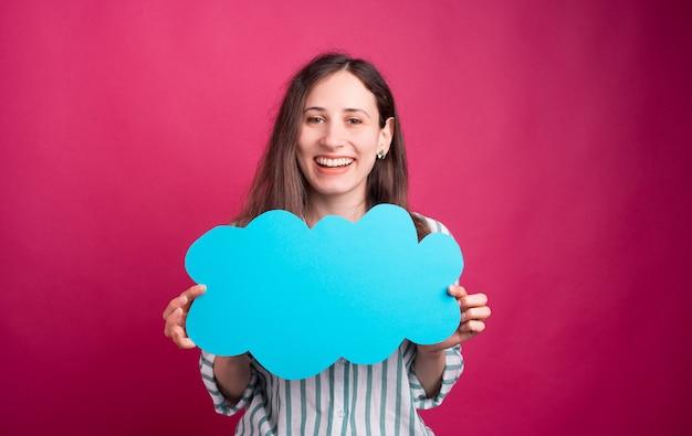 Vrolijke jonge vrouw houdt een blauwe wolk op roze