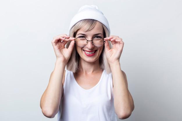 Vrolijke jonge vrouw houdt een bril in een wit t-shirt op een lichte achtergrond.