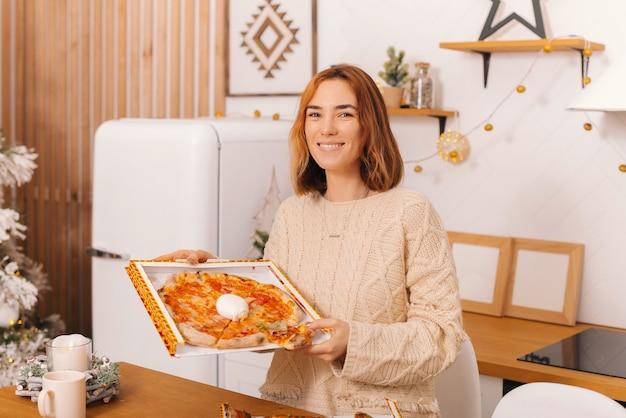 Vrolijke jonge vrouw houdt een doos italiaanse authentieke pizza vast.