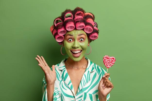 Vrolijke jonge vrouw houdt hand omhoog, houdt lolly vast, glimlacht breed, past schoonheidsmasker toe om er jong uit te zien, maakt kapsel met haarrollers, geïsoleerd op groene muur. hairstyling, gezichtsverzorging