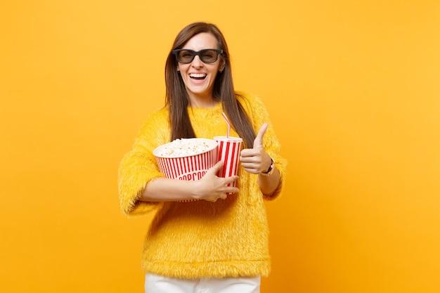 Vrolijke jonge vrouw in 3d imax-bril kijken naar filmfilm, met emmer popcorn, kopje cola of frisdrank, duim opdagen geïsoleerd op gele achtergrond. mensen oprechte emoties in de bioscoop, levensstijl.