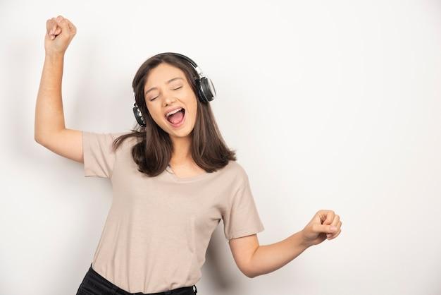 Vrolijke jonge vrouw in beige overhemd dansen en luisteren muziek in hoofdtelefoons.