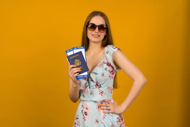 Vrolijke jonge vrouw in blauwe jurk met bloemen en zonnebril houdt vliegtickets met een paspoort op een gele achtergrond. verheugt zich over de hervatting van het toerisme na de coronoviruspandemie.