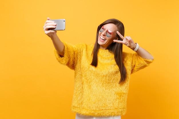 Vrolijke jonge vrouw in bont trui hart bril met overwinning teken doen selfie schot op mobiele telefoon geïsoleerd op heldere gele achtergrond. mensen oprechte emoties levensstijl. reclame gebied.