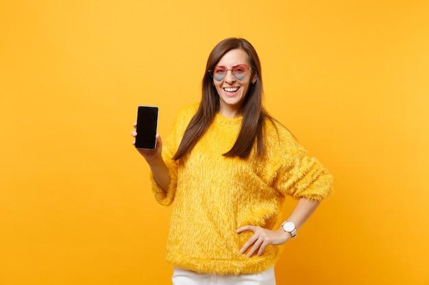 Vrolijke jonge vrouw in bonttrui, hartbril met mobiele telefoon met leeg zwart leeg scherm geïsoleerd op felgele achtergrond. mensen oprechte emoties, lifestyle concept. reclame gebied.