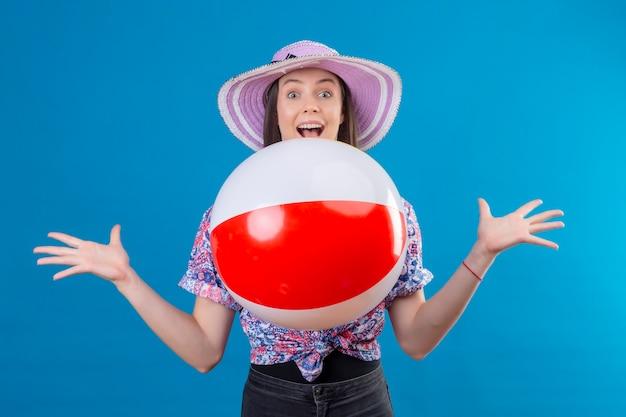 Vrolijke jonge vrouw in de zomerhoed die het gooien van opblaasbare bal draagt ?? die met gelukkig gezicht glimlacht dat zich over blauwe ruimte bevindt