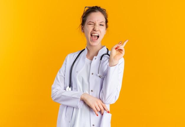 Vrolijke jonge vrouw in doktersuniform met stethoscoop knippert met haar ogen en gebaren overwinningsteken