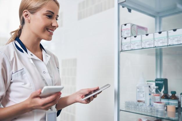 Vrolijke jonge vrouw in een medisch kantoor dat in de buurt van een kast staat met medicijnen tijdens het gebruik van tablet en smartphone