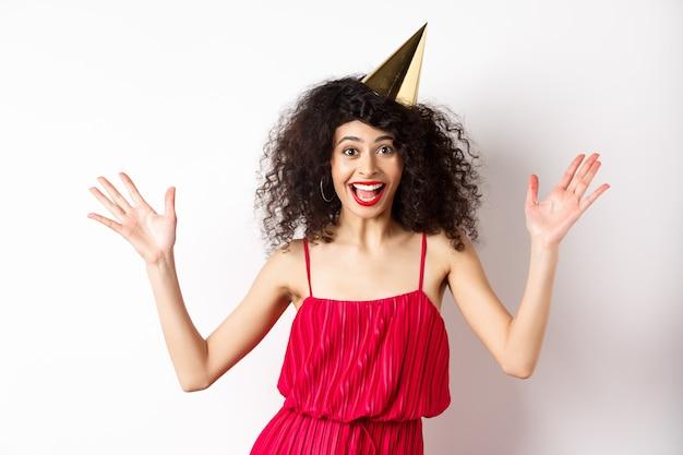 Vrolijke jonge vrouw in een rode jurk, verjaardag vieren, feestmuts dragen en glimlachen, schreeuwen van vreugde, staande op een witte achtergrond.