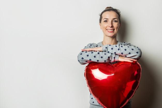 Vrolijke jonge vrouw in een trui legde haar handen op een hart-luchtballon op een lichte achtergrond. valentijnsdag concept. zoek een geliefde.