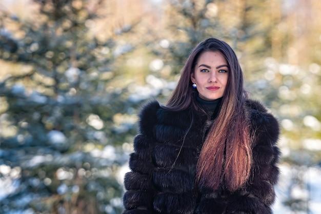Vrolijke jonge vrouw in een warme bontjas genieten van een winterdag in het besneeuwde bos