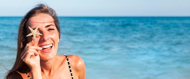 Vrolijke jonge vrouw in een zwembroek met een zeester op het strand. banier.