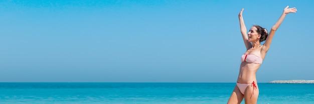 Vrolijke jonge vrouw in een zwempak met opgeheven handen tegen de muur van de zee