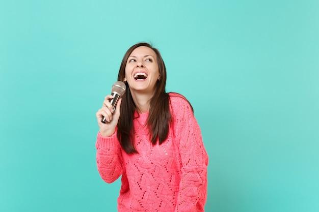 Vrolijke jonge vrouw in gebreide roze trui opzoeken in de hand, zingen lied in microfoon geïsoleerd op blauwe turquoise muur achtergrond, studio portret. mensen levensstijl concept. bespotten kopie ruimte.