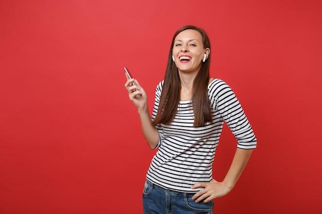 Vrolijke jonge vrouw in gestreepte kleding met draadloze koptelefoon met mobiele telefoon, luisteren naar muziek geïsoleerd op heldere rode achtergrond. mensen oprechte emoties, lifestyle concept. bespotten kopie ruimte.
