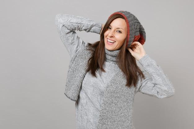 Vrolijke jonge vrouw in grijze trui muts en sjaal handen op het hoofd geïsoleerd op een grijze achtergrond in de studio. gezonde mode levensstijl mensen oprechte emoties koude seizoen concept. bespotten kopie ruimte.