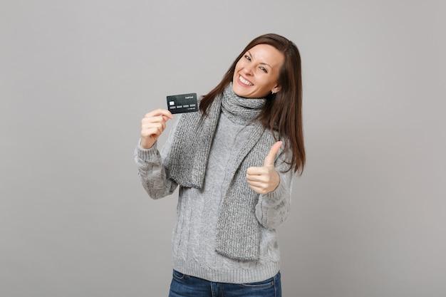 Vrolijke jonge vrouw in grijze trui, sjaal met duim omhoog houd creditcard geïsoleerd op een grijze achtergrond. gezonde mode levensstijl mensen oprechte emoties koude seizoen concept. bespotten kopie ruimte.