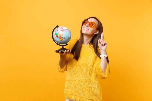 Vrolijke jonge vrouw in oranje hart brillen dromen over reizen, wijzende wijsvinger omhoog houden wereldbol geïsoleerd op gele achtergrond. mensen oprechte emoties, levensstijl. reclame gebied.