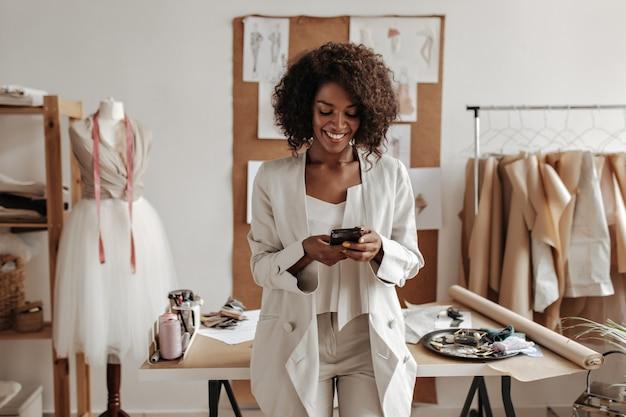 Vrolijke jonge vrouw in oversized witte jas en broek poseert in het kantoor van modeontwerper