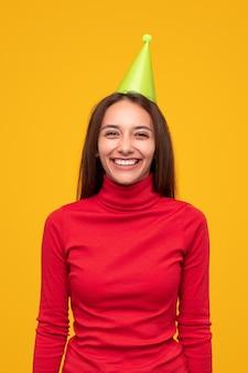 Vrolijke jonge vrouw in rode coltrui en groene feestmuts lachen en kijken terwijl ze plezier hebben tijdens de vakantieviering