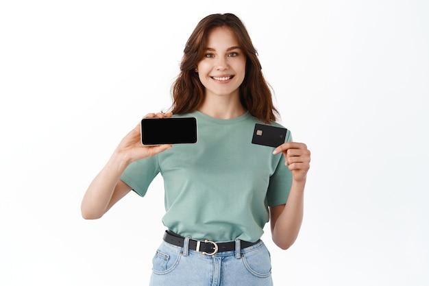 Vrolijke jonge vrouw in t-shirt demonstreerde horizontaal leeg smartphonescherm en plastic creditcard, staande tegen een witte muur