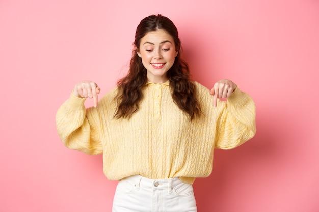 Vrolijke jonge vrouw in trui, wijzend en naar beneden kijkend met een blije glimlach, geïntrigeerd door promo-aanbod, staande over roze muur.