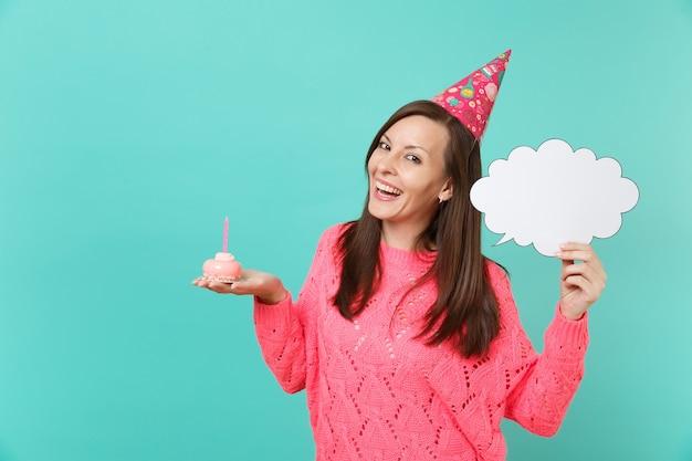 Vrolijke jonge vrouw in verjaardagshoed in hand taart met kaars leeg leeg say cloud, tekstballon voor promotionele inhoud geïsoleerd op blauwe achtergrond. mensen levensstijl concept. bespotten kopie ruimte.