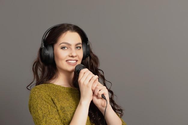 Vrolijke jonge vrouw in vrijetijdskleding met koptelefoon zingen lied in de microfoon, bespotten kopie ruimte