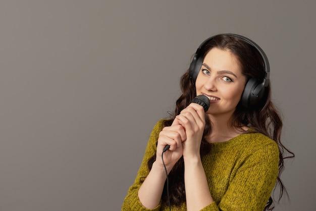 Vrolijke jonge vrouw in vrijetijdskleding met koptelefoon zingen lied in de microfoon