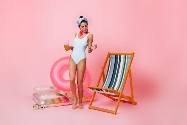 Vrolijke jonge vrouw in wit zwempak die dichtbij chaise longue dansen