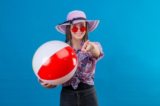 Vrolijke jonge vrouw in zomerhoed die rode zonnebril draagt die opblaasbare bal houdt die met vinger naar camera richt met blij gezicht glimlachend status over blauwe ruimte