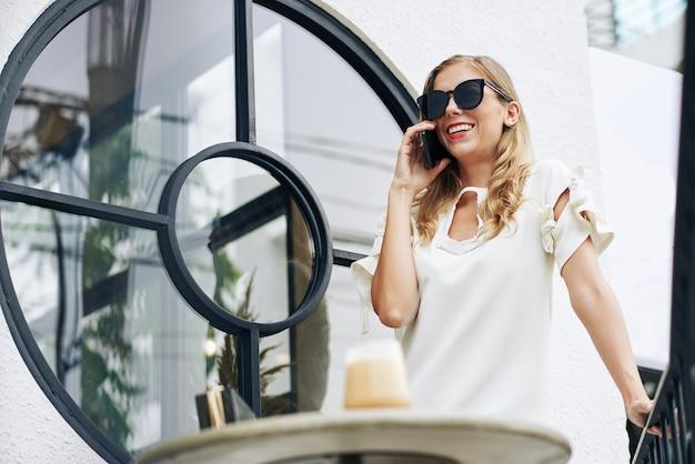 Vrolijke jonge vrouw in zonnebril staan aan café tafel en praten over de telefoon