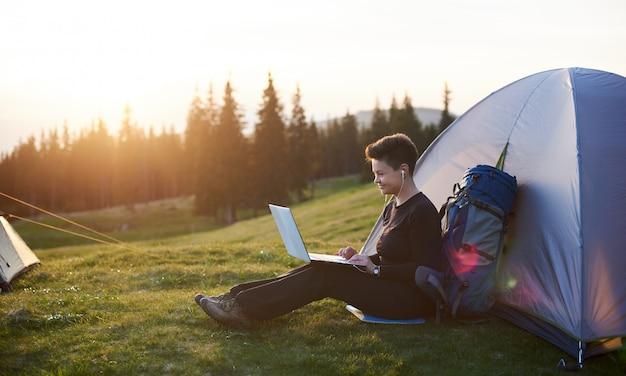 Vrolijke jonge vrouw kamperen buiten zitten in de buurt van haar tent met behulp van laptop