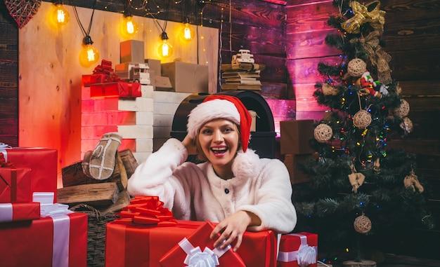 Vrolijke jonge vrouw kerstkostuum dragen over houten muur evenement mooie vrouw met kerstmis...