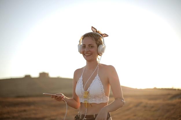 Vrolijke jonge vrouw, luisteren naar muziek met een koptelefoon en dansen