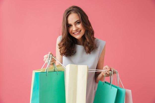 Vrolijke jonge vrouw met boodschappentassen.