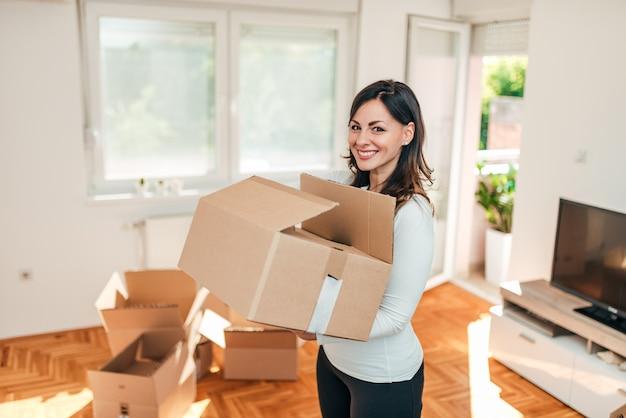 Vrolijke jonge vrouw met doos. verhuisdag.