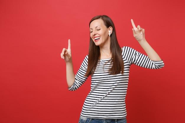 Vrolijke jonge vrouw met draadloze koptelefoon dansen, wijsvingers omhoog wijzen, muziek luisteren geïsoleerd op felrode muur achtergrond. mensen oprechte emoties, lifestyle concept. bespotten kopie ruimte.