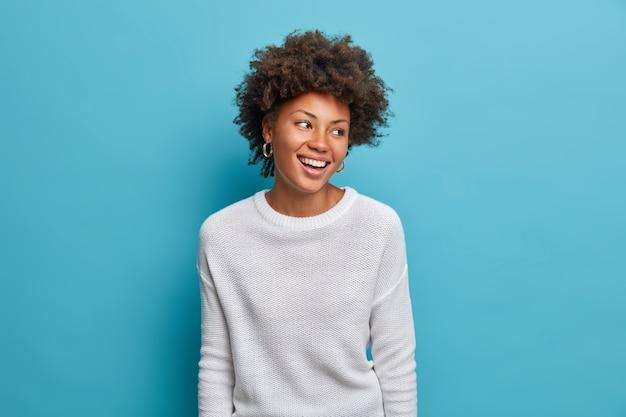 Vrolijke jonge vrouw met een donkere huid en een brede glimlach, perfecte tanden, voelt zich zorgeloos en enthousiast, kijkt vrolijk opzij, staat vermaakt, draagt een casual witte trui,