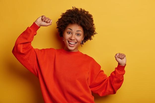 Vrolijke jonge vrouw met een donkere huid heft beide armen op, voelt zich gelukkig, gaat naar een geweldig feest, gekleed in een oversized trui