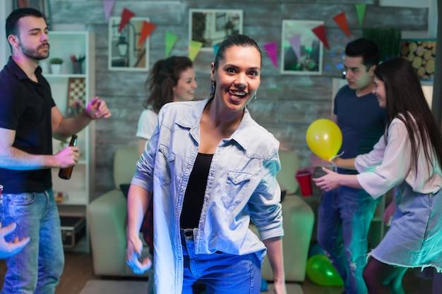 Vrolijke jonge vrouw met een grote glimlach die naar de camera kijkt tijdens het feesten met haar vrienden.
