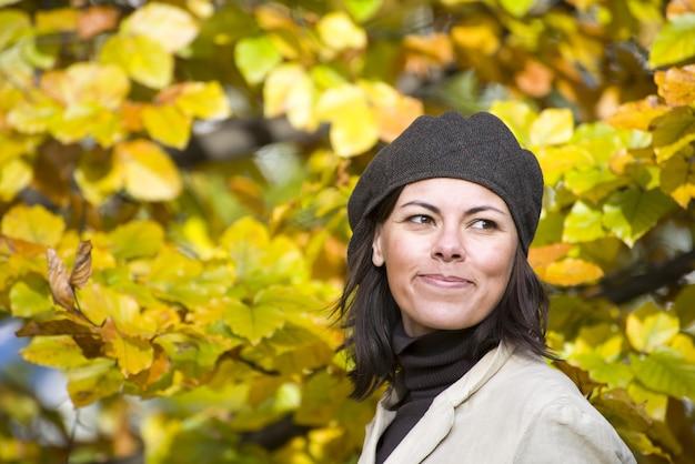 Vrolijke jonge vrouw met een hoed met mooie gele herfstbladeren in de
