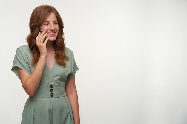 Vrolijke jonge vrouw met een mobiele telefoon in de hand staan, een vriend bellen en vreugdevol glimlachen, in een goede bui